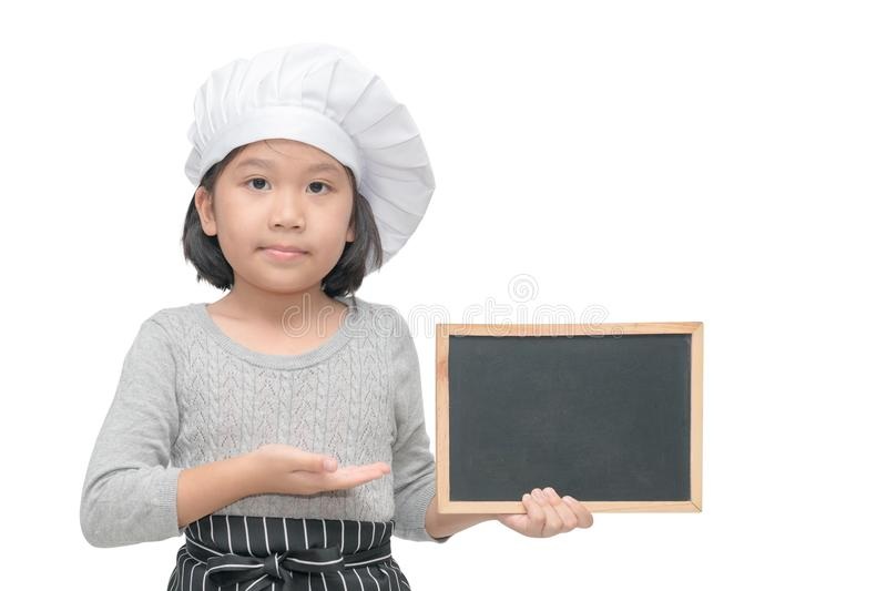 Little asian girl chef in uniform cook holding blackboard royalty free stock photography