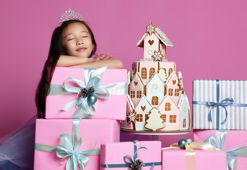 Little asian girl in crown and purple dress with many present gift boxes and ginger cookie cake birthday celebration stock photography