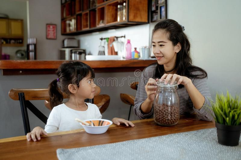 Little asian girl eating cereal for breakfast with mom royalty free stock photography