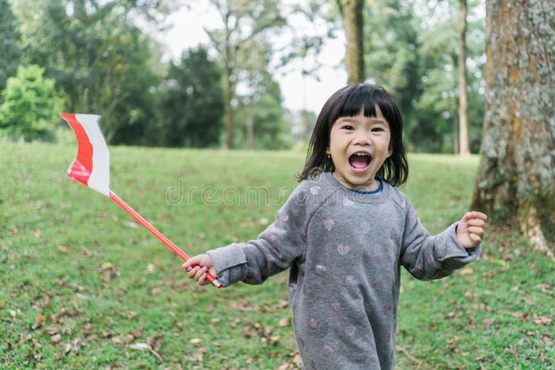 Little asian girl flapping indonesia national flag with smile. When walking in the park royalty free stock photography