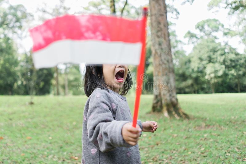 Little asian girl flapping indonesia national flag with smile. When walking in the park stock photo