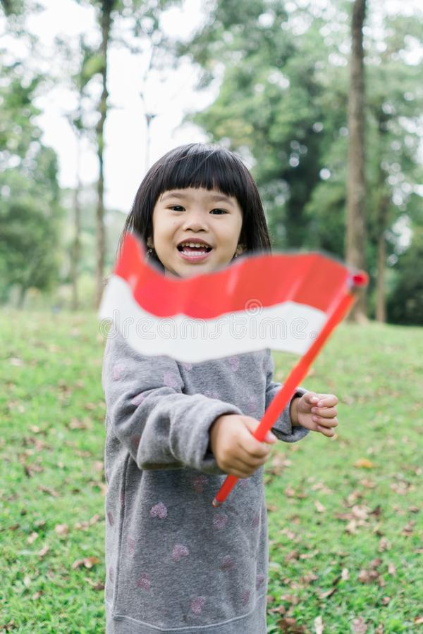 Little asian girl flapping indonesia national flag with smile. When walking in the park stock images