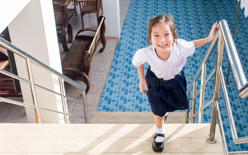Little Asian girl going up the stairs in the school stock images