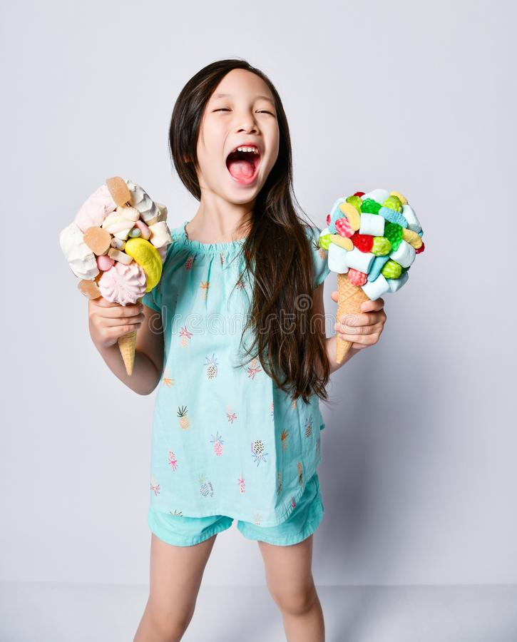 Little asian girl kid with eyes closed with happiness holds her treasure two big ice-cream in waffles cones with tasty toppings stock photography