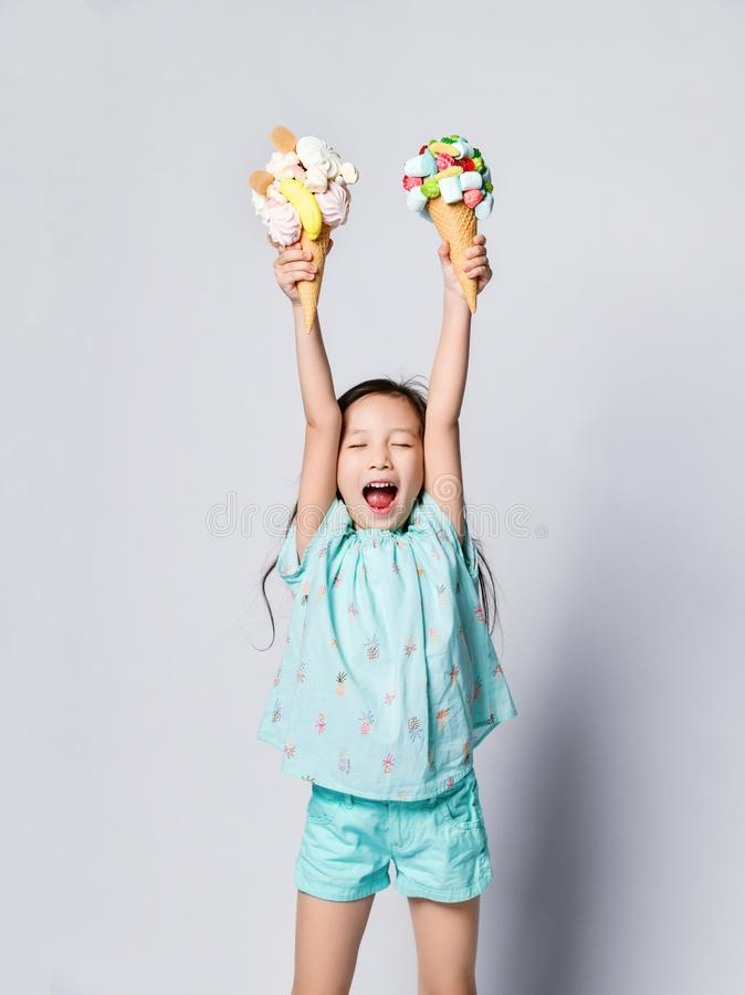 Little asian girl kid with eyes closed with happiness holds up high two sweet big ice-cream in waffles cones with tasty toppings stock photo