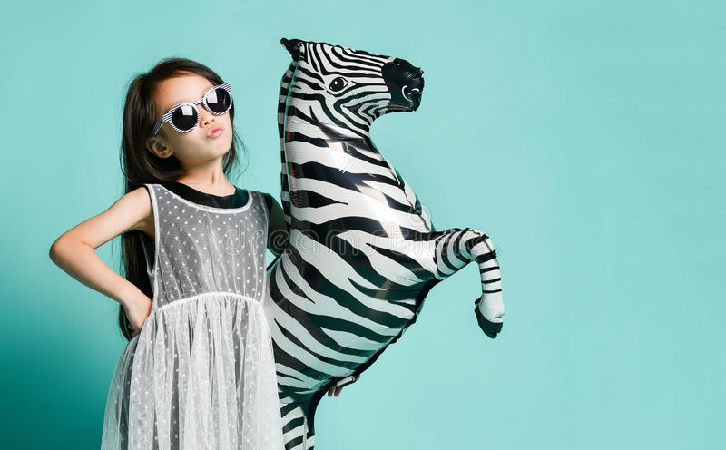 Little asian girl kid hold big zebra balloon present for birthday party in stylish fashion cloth and sunglasses on blue mint royalty free stock photo