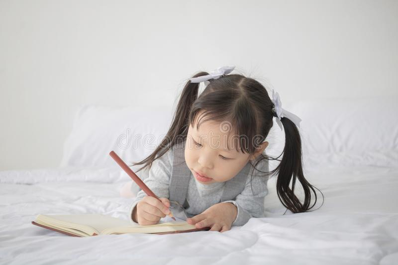 Little Asian girl lying on bed and writing alphabet on notebook stock images