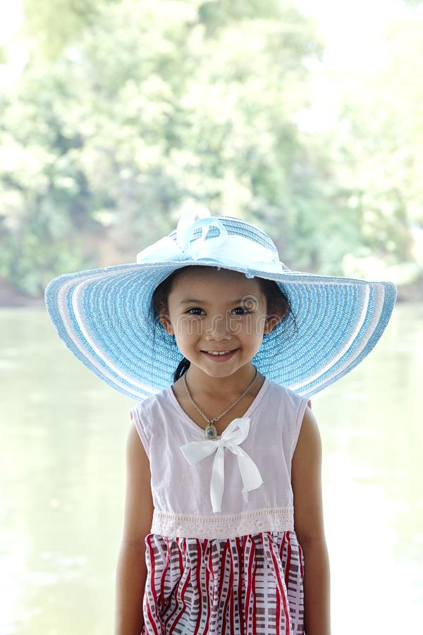 Little Asian Girl outdoors in summer hat stock image