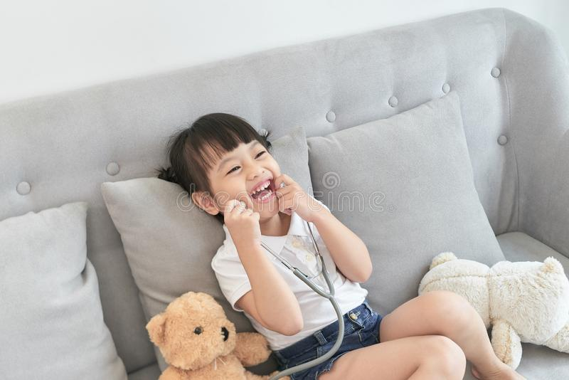 Little asian girl play with baby doll toy.Little asian girl hold stethoscope in hand and check baby doll toy royalty free stock photos