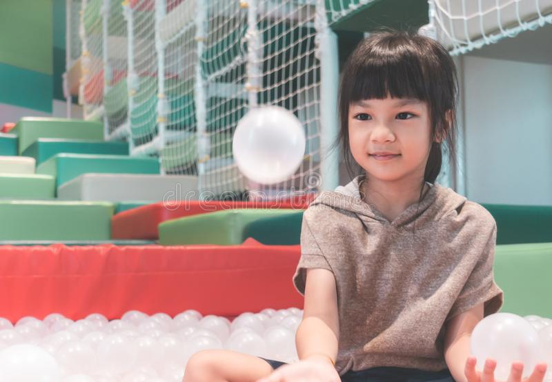 Little asian girl playing with ball in ball pit playground stock photos