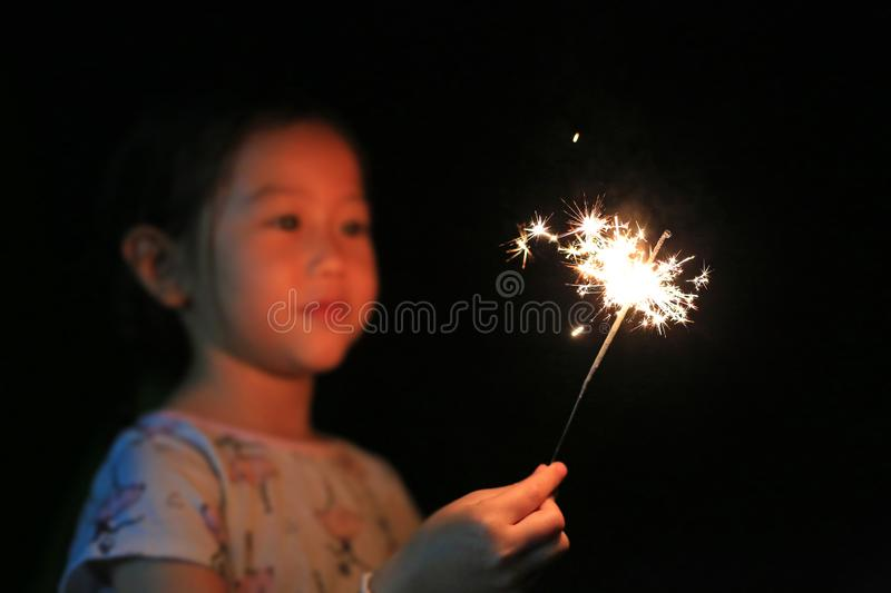 Little Asian girl playing fire sparklers in the dark. Little Asian girl playing fire sparklers in the dark royalty free stock photos