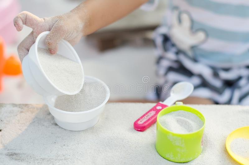 Little asian girl playing with sand stock photos