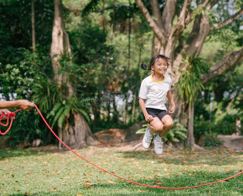 Little Asian girl playing with skipping rope jumping at green nature park. royalty free stock photography