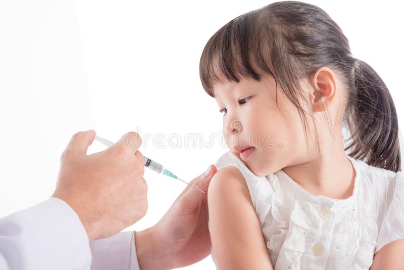 Girl receiving vaccination from doctor isolated over white. Little asian girl receiving vaccination from doctor isolated over white background stock photos