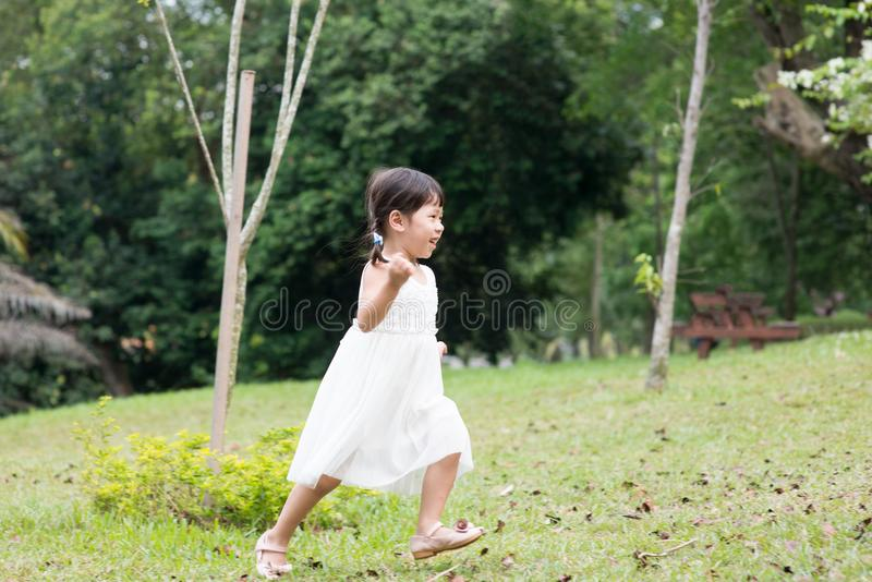 Little Asian girl running outdoors royalty free stock image