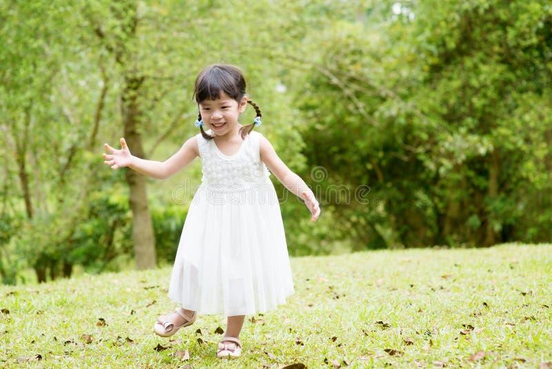 Little Asian girl running at park stock photography