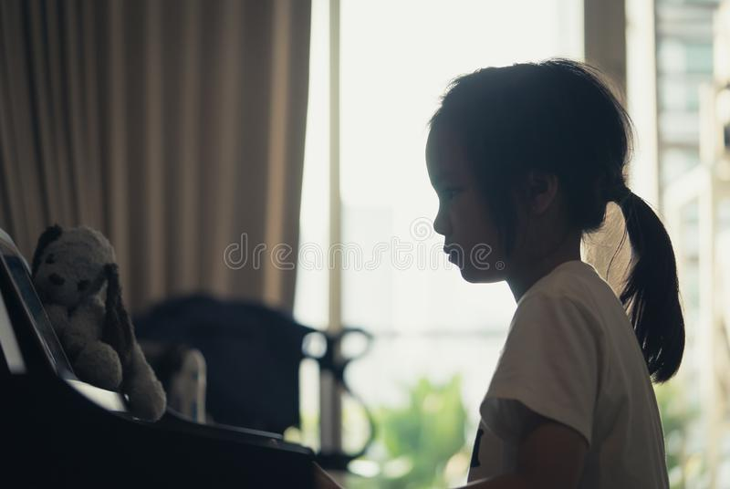 Little girl silhouette playing piano at home stock photo