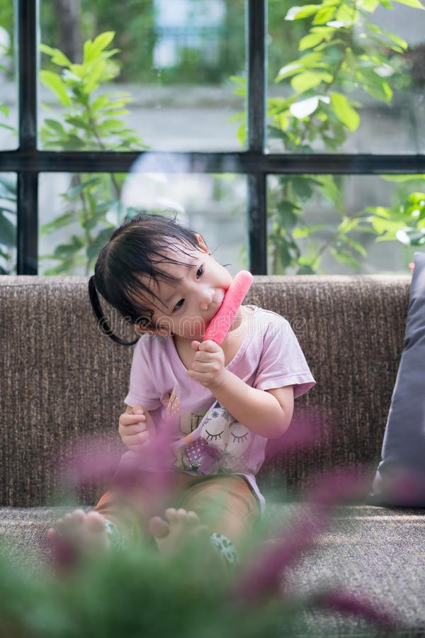 Little asian girl sitting happily eating ice cream sticks in the cafe stock photos
