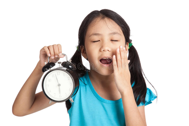 Little asian girl sleepy with a clock royalty free stock image