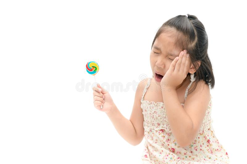 Little Asian girl suffering from toothache and holding candy. In hand isolated on white background, Dental problem concept royalty free stock photos