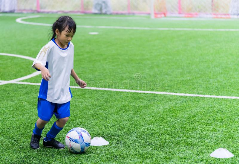 Little Asian girl training in indoor soccer field. Little Asian girl is training in indoor soccer field royalty free stock images