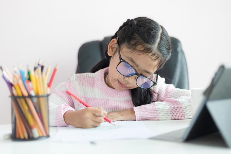 Little Asian girl using the pencil to write on the paper doing homework and smile with happiness for education concept select. Focus shallow depth of field royalty free stock images