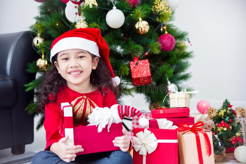 Girl wearing santa hat and smiles while opening christmas gift at home stock photo