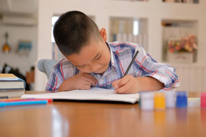asian kid boy child schoolboy drawing picture. children activity royalty free stock photos