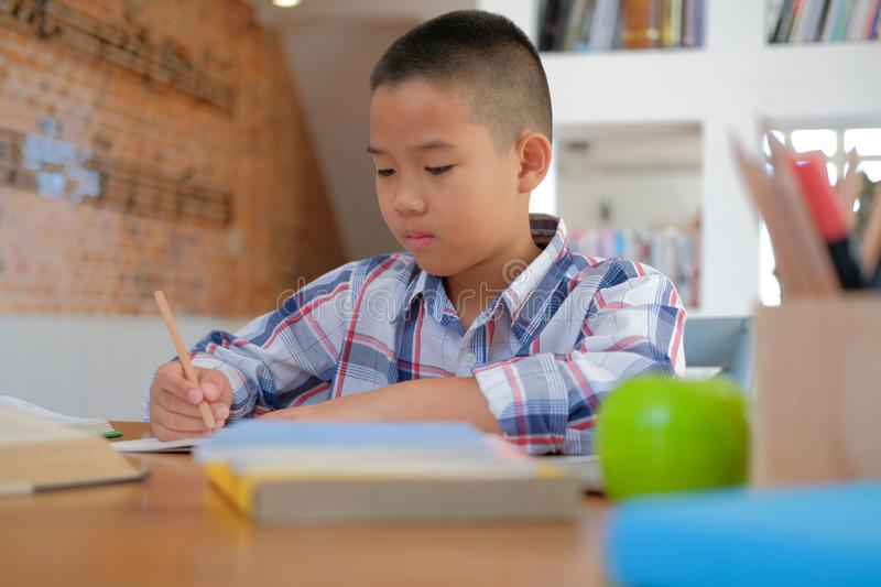 little asian kid boy schoolboy writing drawing on notebook. child children doing homework. stock photography