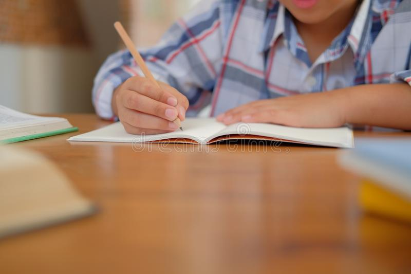 little asian kid boy schoolboy writing drawing on notebook. child children doing homework. stock photo