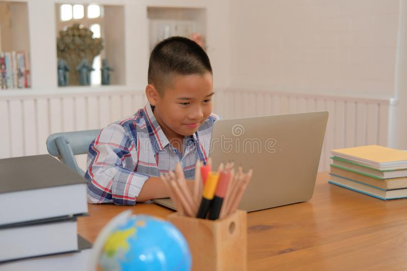 little asian kid boy studying doing homework. child learning les royalty free stock image