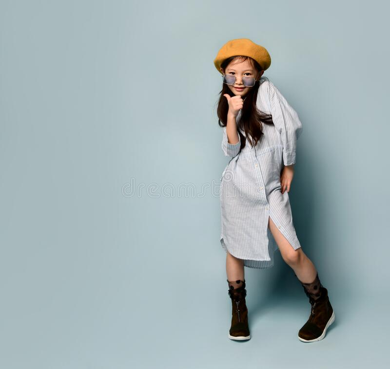 Free Little Asian Kid In Sunglasses, Oversized Shirt Dress, Brown Beret, Boots. She Kissing You, Posing On Blue Background. Full Length Royalty Free Stock Photo - 171225585