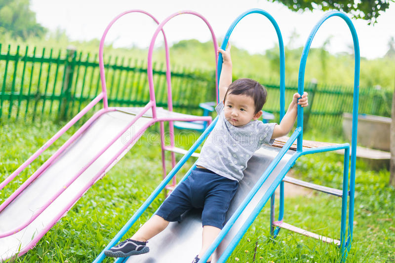 Little Asian kid playing slide at the playground royalty free stock photo