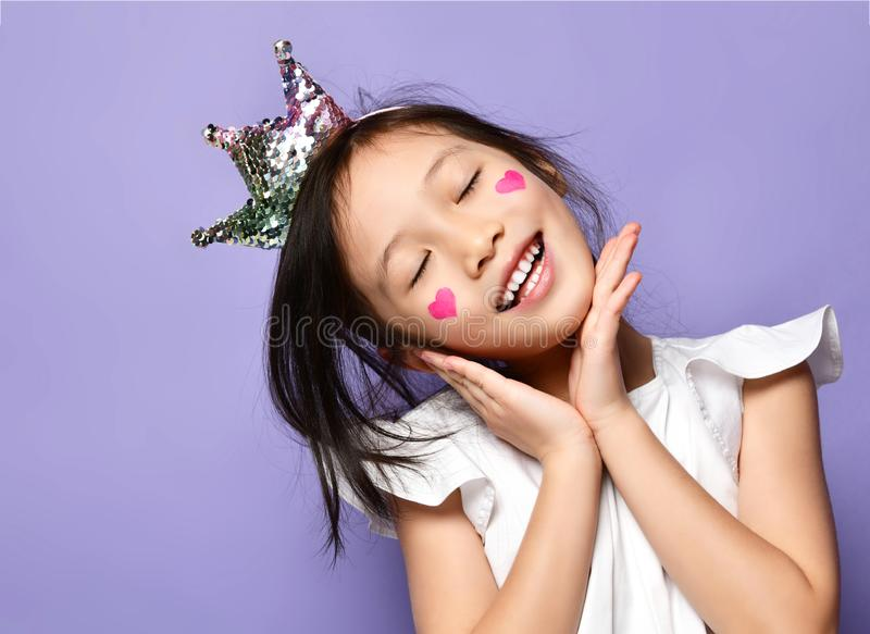 Asian Korean kid girl princess in crown closeup portrait Happy smiling laughing with a painted red hearts sign on cheeks royalty free stock photo