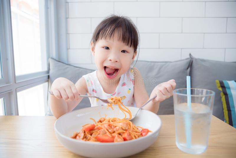Pretty girl using fork eating spaghetti by herself royalty free stock images