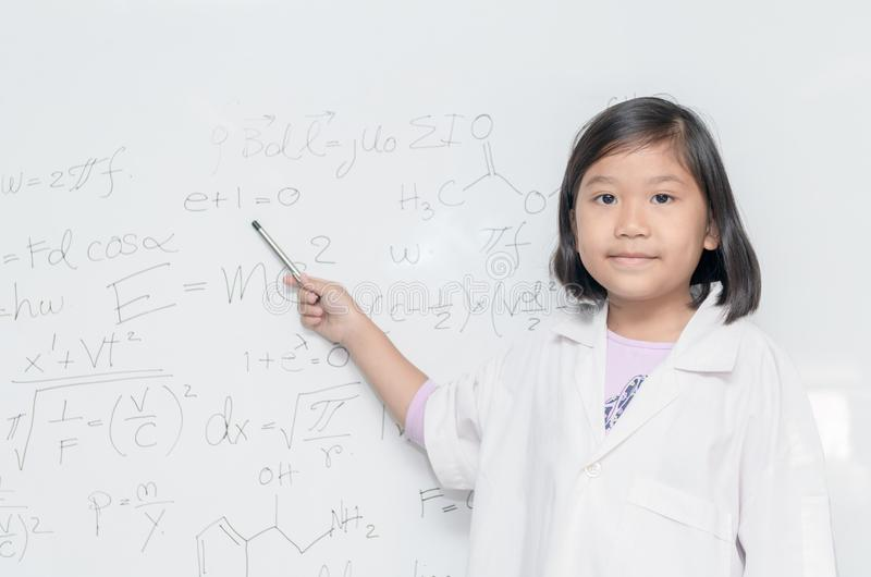 Little asian scientist girl pointing on white board stock images