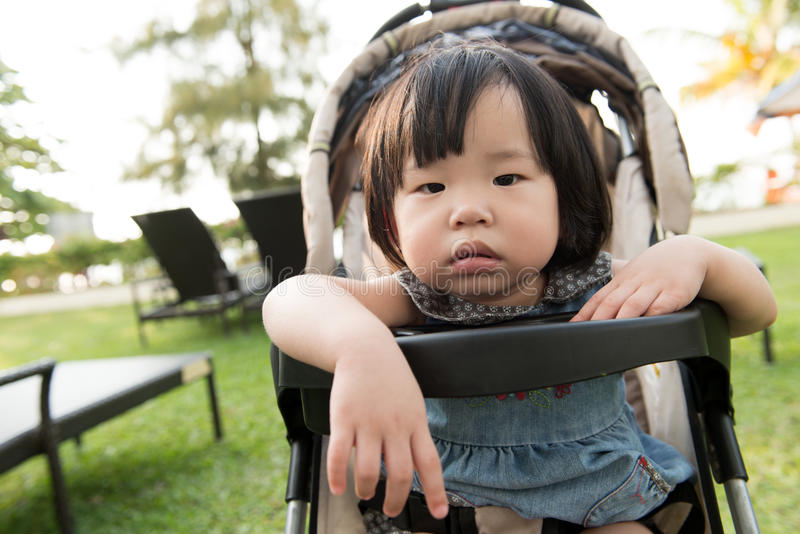Little Asian toddler. In sitting stroller at the resort beach stock photo