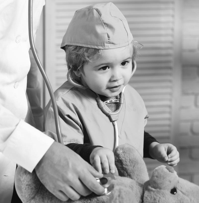 Little assistant examine teddy bear. Father and kid with curious and happy face playing doctor. Healthcare and childhood concept. Male and boys hands hold stock images