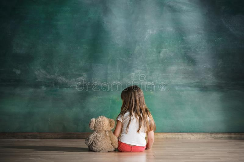 Little girl with teddy bear sitting on floor in empty room. Autism concept royalty free stock images