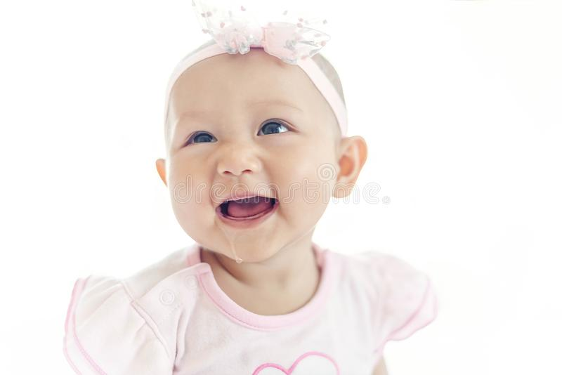 Little baby Asian girl 7 months with pink dress looking at her mother on white bed stock photography