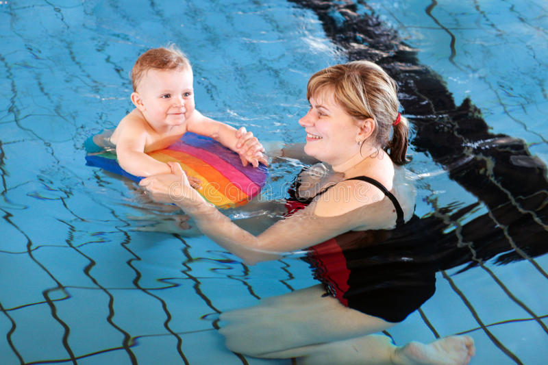 Little baby with blue eyes learning to swim. With mother royalty free stock photo