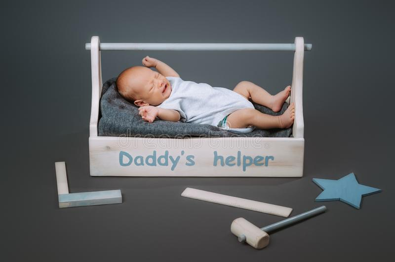 Little baby in bodysuit crying while lying in wooden toolkit with daddys. Helper lettering stock photography
