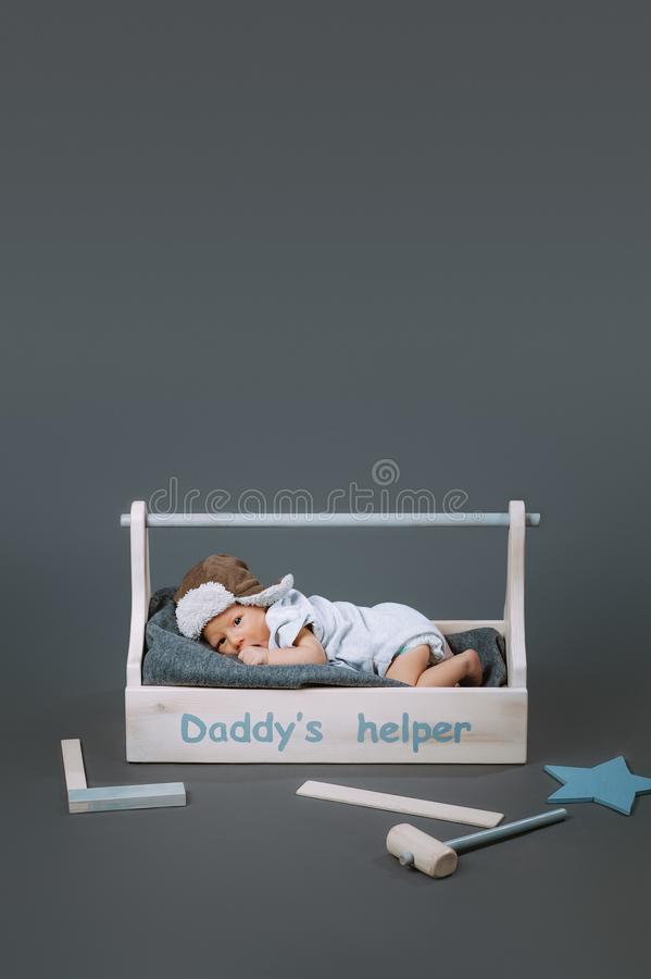Little baby in bodysuit lying in wooden toolkit with daddys helper lettering and hammer. Near by royalty free stock images