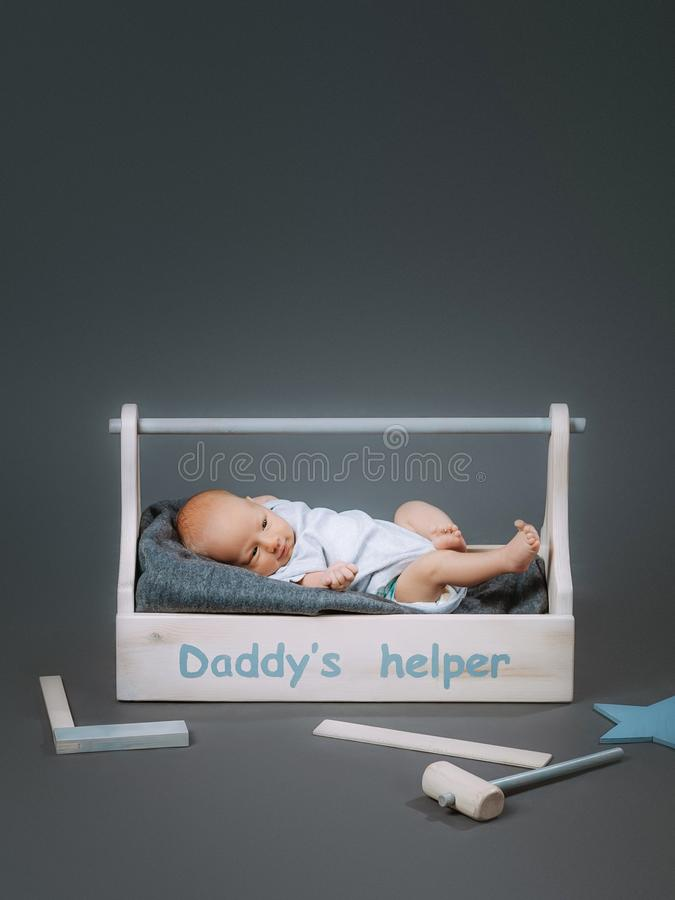 Little baby in bodysuit lying in wooden toolkit with daddys helper lettering and hammer. Near by stock photos