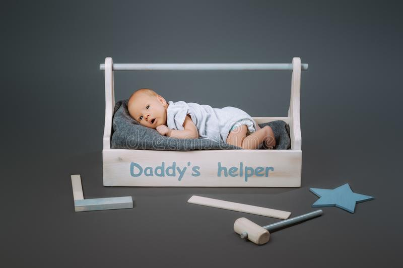 Little baby in bodysuit lying in wooden toolkit with daddys helper lettering and hammer. Near by royalty free stock photo