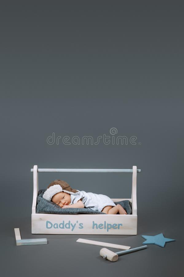 Little baby in bodysuit lying in wooden toolkit with daddys helper lettering and hammer. Near by stock image