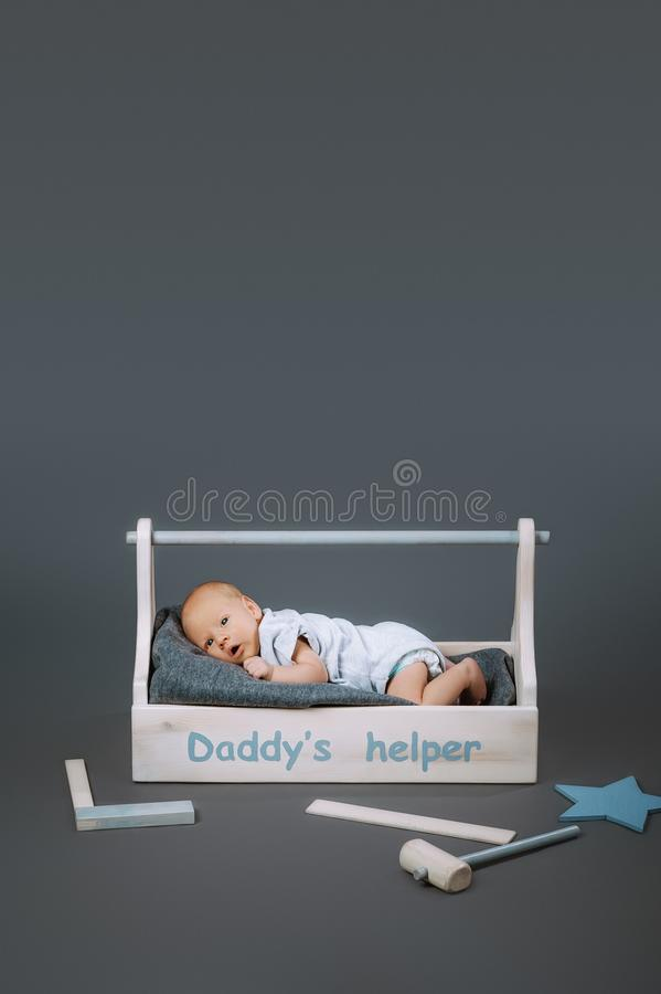 Little baby in bodysuit lying in wooden toolkit with daddys helper lettering and hammer. Near by stock images
