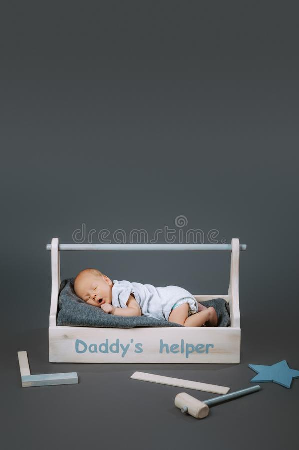 Little baby in bodysuit yawning in wooden toolkit with daddys helper lettering and hammer. Near by royalty free stock photos