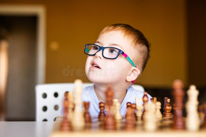 Little baby boy with down syndrome with big blue glasses playing chess in kindergarten.  stock photography