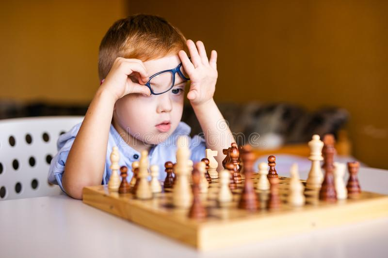 Little baby boy with down syndrome with big blue glasses playing chess in kindergarten.  stock images